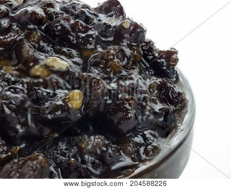 extreme macro shot of homemade Christmas traditional mincemeat home made with mixed fruits and brandy in a glass bowl on an isolated white background