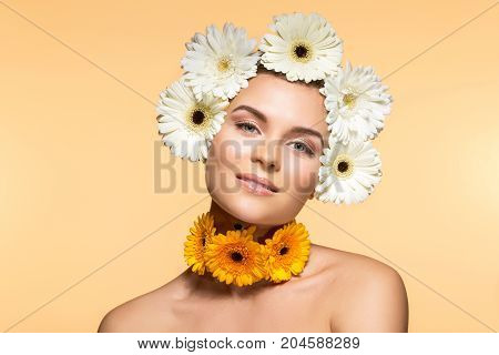 beautiful young woman with natural makeup and white Herberas flowers on head and neck. beauty shot on yellow background. copy space.