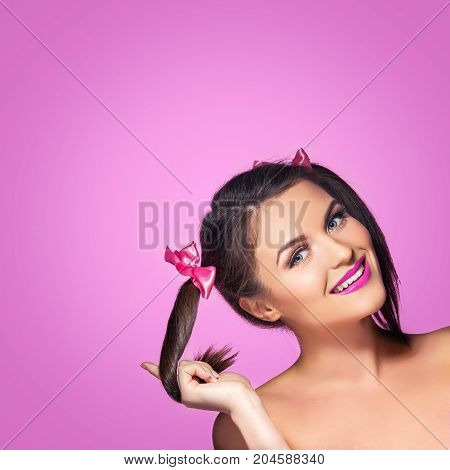 beautiful young woman with pink makeup and two girly ponytails. Beauty shot on pink background. copy space.