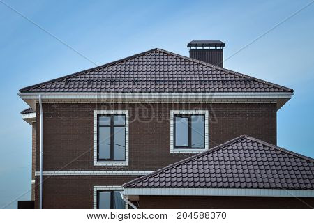The upper part of the new brick brown house with tiled roof.