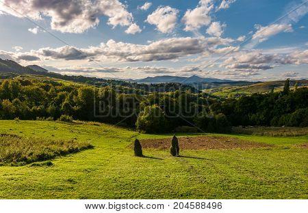 Haystack On Fields In Mountainous Rural Area