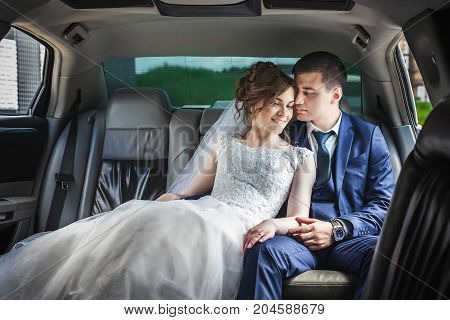 portrait of newlywed couple hugging in the car. Bride in beautiful white wedding dress and asian groom in dark blue suit. Hugging and smiling
