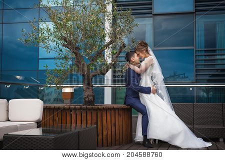 portrait of newlywed couple hugging in luxury restaurant. Bride in beautiful white wedding dress and asian groom in dark blue suit. Hugging and smiling