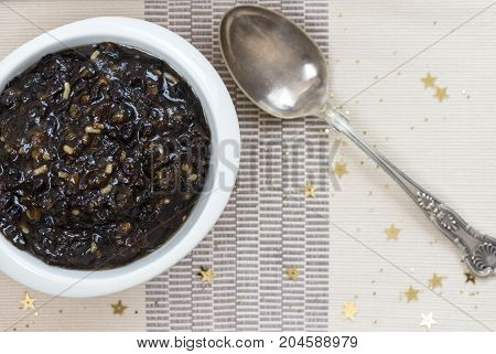 horizontal image of homemade traditional Christmas mincemeat made with mixed fruit and brandy in a white bowl focus on the subject background de focused to ad copy space