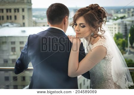 beautiful newlywed couple. caucasian smiling bride in beautiful white wedding dress looking down and asian groom in dark blue suit over city landscape. back view