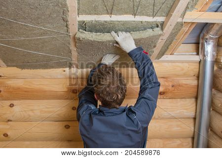 Worker installing insulation panels of mineral wool into roof of house. Roofing construction and thermal protection.