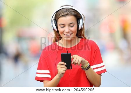 Teen Walking And Listening Music On The Street