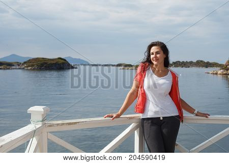 Young woman against beautiful view on norwegian fjords. outdoor shot in Norway. copy space.