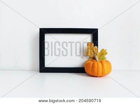 Black blank wooden frame mockup with an orange pumpkin and golden oak leaves lying on the white table. Poster product design, styled stock feminine photography. Home decor. Autumn, fall concept.