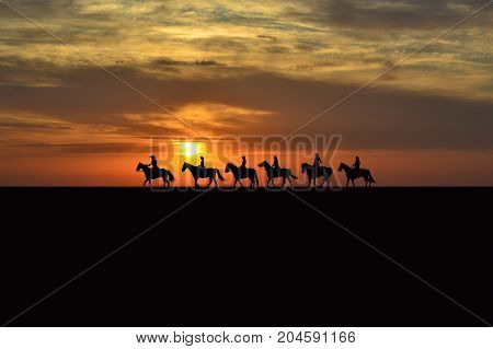 Landscape of horse rider silhouettes at sunrise