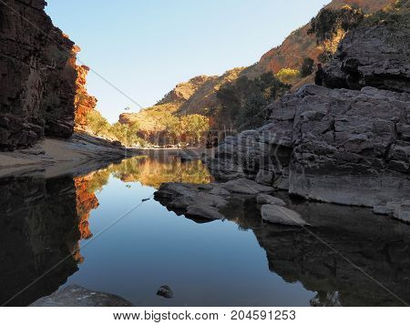 Reflections in the dark waters of Ormiston Gorge with red glowing cliffs in the evening sun Northern Territory Australia 2017