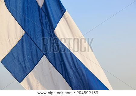 Finnish flag under a blue sky. Finland symbol. Europe. Horizontal