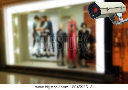CCTV security indoor camera system operating at showcases fashion clothes display in department store shopping mall fashion shopping surveillance security and safety technology concept