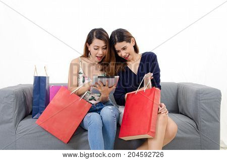 two young friends asian woman watching special offer in her tablet with shopping bags on sofa at home white background lifestyle smart internet technology online shopping and payment online concept