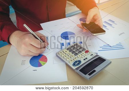 hand working and writing with smart phone calculate finances about cost with business strategy diagram report on desk at home office income and expenses money cost savings business economy concept