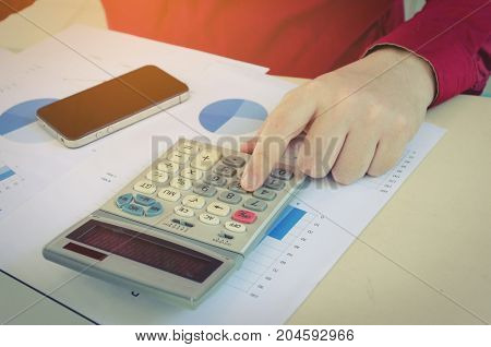 young man calculate finances about cost with calculator mobile smart phone and business strategy diagram report on desk at home office income and expenses money cost savings and economy concept