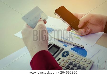 hand paying with credit card and entering security code with mobile smart phone calculator and income and expenses strategy diagram report on desk at home office payment and shopping online concept