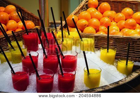 Glass cups of fresh fruit smoothies with drinking straws displayed in a pile of ice in the store