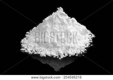 heap of white powder on black background