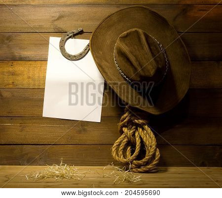 Cowboy accessories hanging on old wooden ranch wall and blank white background for text