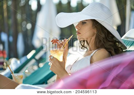 Beautiful girl in a white swimsuit and hat lies on the sun lounge outdoors. She holds a cocktail in the hands and looks forward with parted lips. Closeup. Horizontal.