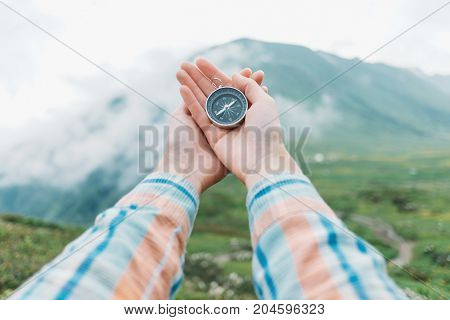 Female explorer searching direction with a compass in summer mountains at foggy weather. Point of view shot.