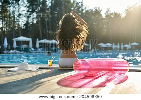 Charming girl with a windy hair in a white swimsuit sits on the pool's edge outdoors. Next to her there is a glass with a cocktail, white hat and a pink swim ring. Shoot from the back. Horizontal.