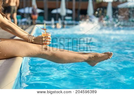 Delightful girl sits on the pool's edge outdoors. She holds an orange cocktail in the hands. Sun shines onto her body. Closeup. Horizontal.