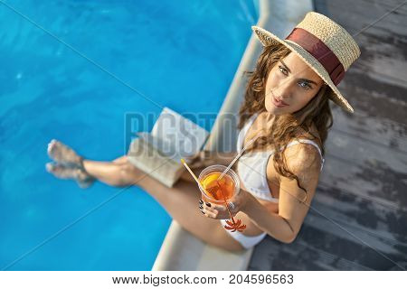 Happy girl in a white swimsuit and a straw hat sits on the pool's edge outdoors and looks into the camera with a smile. She holds her feet in the water and holds a cocktail and a book. Horizontal.
