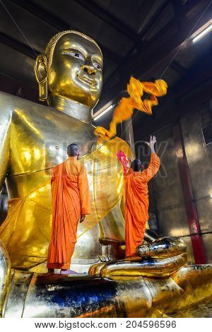 Chachoengsao Thailand - July 13 2013: Chinese Buddhist monks dressing golden Buddha Image body with yellow robes in Chinese shrine in Chachoengsao Thailand