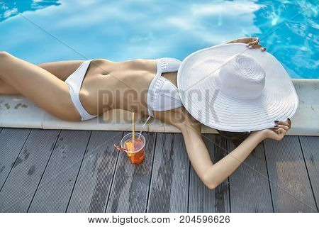 Fancy girl in a white swimsuit lies on the pool's edge outdoors. She holds a big hat which closes her face. Next to her there is an orange cocktail. Sun shines onto her body. Top view photo.
