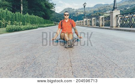 Fashionable tattoed guy in glasses sitting on longboard outdoor.