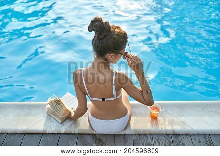 Attractive girl in a white swimsuit and sunglasses sits on the pool's edge outdoors. She holds a book in the left hand and holds right hand on the sunglasses. Next to her there is an orange cocktail.