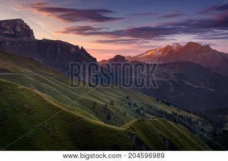 View on illuminated Marmolada highest peak in Dolomites from Sella pass at beautiful sunrise.