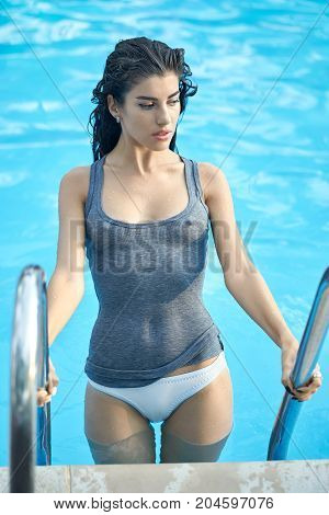 Hot girl with wet hair in a white swimsuit and gray sleeveless stands on the stair in the swimming pool outdoors. She looks to the side with parted lips. Sun shines onto her body. Vertical.