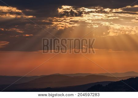 Colorful cloud formation with idyllic sun rays on mountain as background.