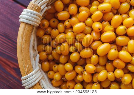 Seabuckthorn in a wooden basket, top view, close-up
