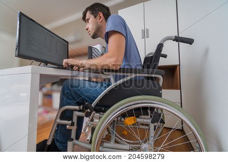 Handicapped Disabled Man On Wheelchair Is Working With Computer