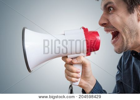 Young Man Is Shouting To Megaphone And Announcing News.