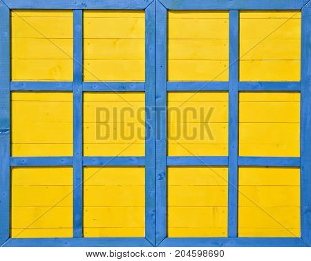 Closeup of an old handmade wooden window painted in unusual bright colors