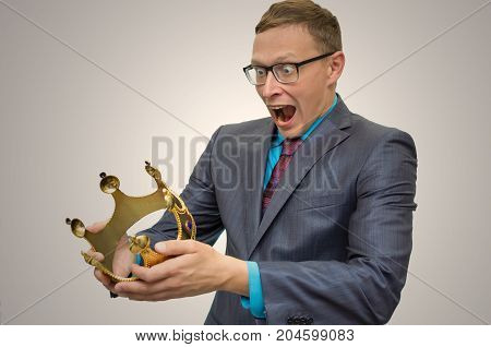 Joy of Victory. Victory in elections. Rise to power. Win prize in lottery. Award ceremony. Success. Mad funny business Man in suit and glasses holding in hands golden crown and stares on her with wide open mouth.