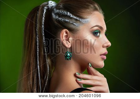 Back view of pretty woman with perfect bronze skin, shiny manicure, long eyelashes, makeup in green colors, and long hair. Beautiful woman with stylish hairstyle and big rounded earring. Beauty.
