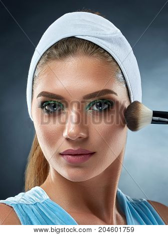 Front view of young girl wearing in bandage on head, making professional makeup, posing at camera with ankle in hand. Beautiful woman cosmetologist drawing blush for herself. Dark studio background.