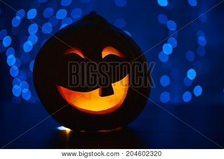 Funny smiling red pumpkin with fire inside and big eyes, prepared for Halloween holiday, sitting on wooden table in dark, against blue lights. Hand made decoration for autumn holiday.