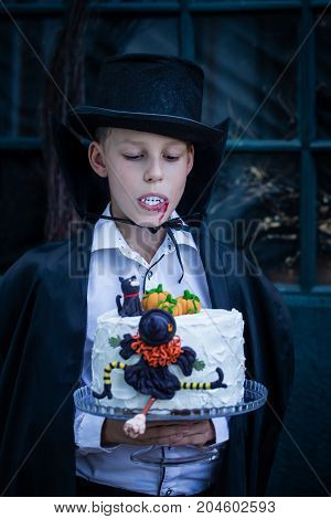 The boy is dressed as a vampire holding a cake