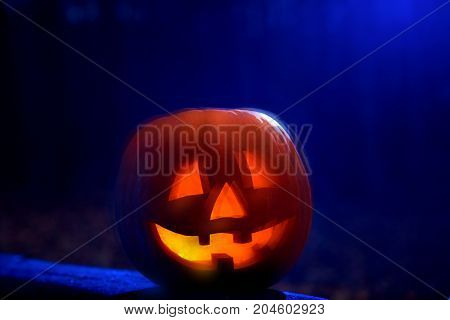 Scary blurry red pumpkin with smoke inside, big eyes, mouth and three tooth. Decoration for Halloween at forest outdoor. Dark blue background.