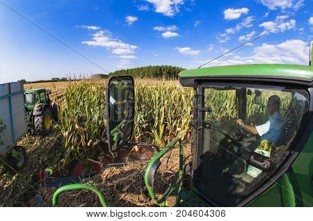 The Combine Driver Looks At A Tractor On The Field