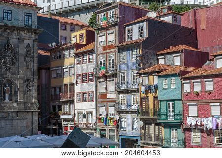 Typical Colorful Portuguese Architecture: Tile Azulejos Facade With Flags, Antique Windows And Balco