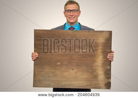 Smiling business man in suit and glasses holding in hands empty bill board with copy space. Advertisement board. Product presentation.