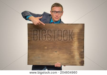 Smiling business man in suit and glasses holding in hands empty bill board with copy space and showing by finger on it. Advertisement board. Product presentation.